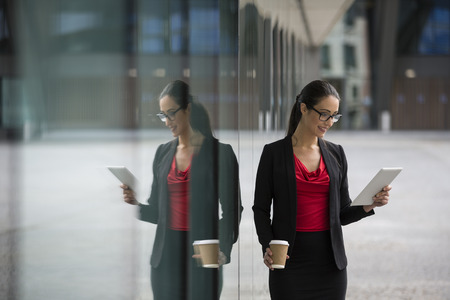 executive woman: Happy Caucasian business woman using a tablet pc outside. Leaning against a glass window showing reflection. Stock Photo