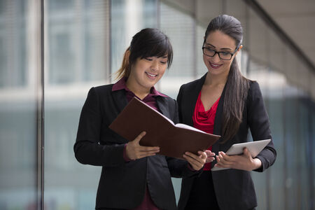 asian business women: Two businesswomen with digital tablet in a modern urban setting. Caucasian and Asian business women.