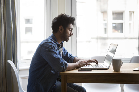 Portrait of an Indian man sitting at a table at home working on a laptop computer. Side View.