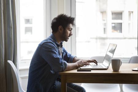 usando computadora: Retrato de un hombre indio que se sienta en una mesa en casa trabajando en un ordenador portátil. Vista lateral.