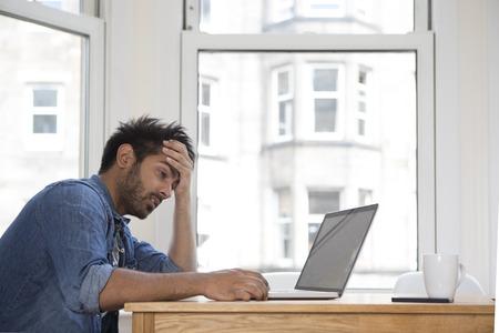 Gestrest en gefrustreerd Aziatische man zittend op zijn laptop.