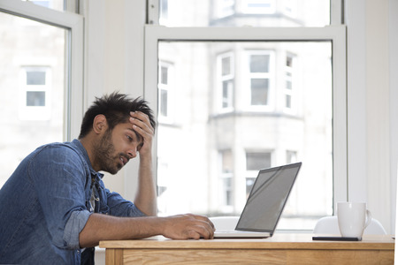 behind: Stressed and frustrated Asian man sitting at his laptop.
