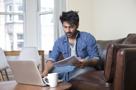 Indian man at home on sofa using a laptop. photo