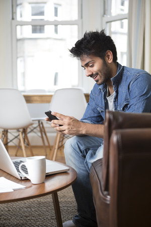 Asian man using a mobile phone and working on his laptop photo