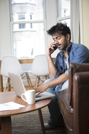 Asian man talking on a mobile phone and working on his laptop at home. photo