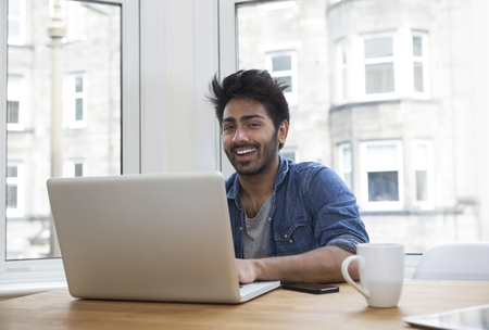 Portrait of an Indian man sitting at a table at home working on a laptop computer.