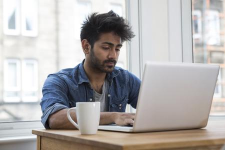 working at home: Retrato de un hombre indio que se sienta en una mesa en casa trabajando en un ordenador port�til.