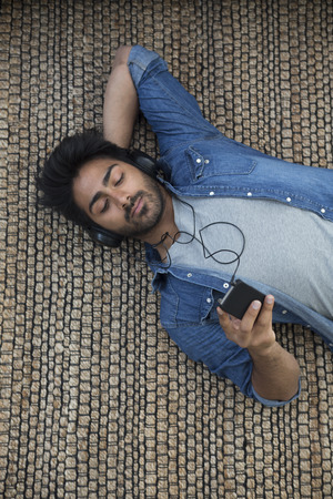 Indian man lying on the floor at home reading his tablet PC. Above view. photo