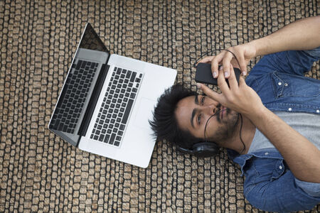 Asian man lying on the floor at home with laptop and phone. Above view photo