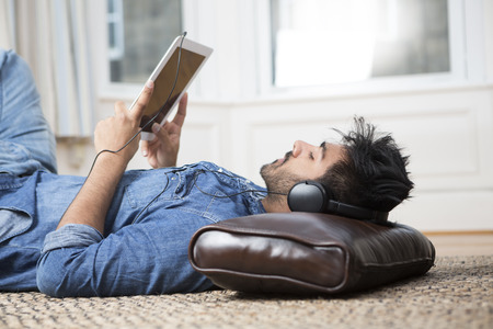 indian style sitting: Asian Man lying on floor at home and using a Tablet PC.