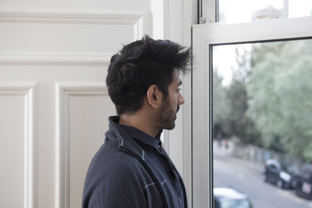 man looking out: Portrait of an Asian man at home looking out of the window. Stock Photo