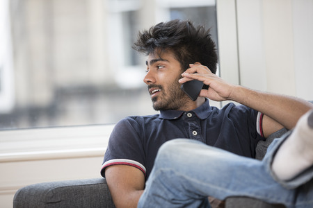 happy young man: Asian Man using his phone at home in the lounge.