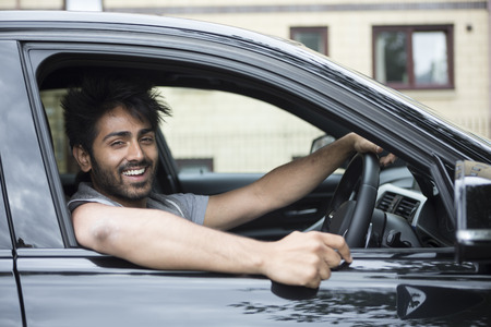 Portrait of a happy Indian man smiling in his new car.