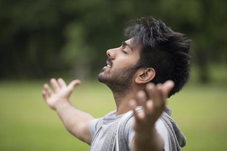 Homme asiatique debout avec les bras levés à l'extérieur. Concept de la liberté, la foi et la célébration. Banque d'images