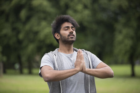 indian yoga: Portrait of young Indian man doing yoga exercise in park