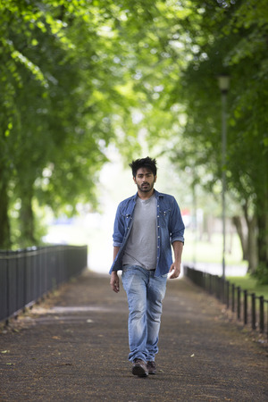 Portrait of a trendy Indian man walking in a city park.