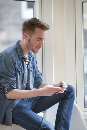 chilling: Cheerful Man using his phone at home in the lounge. Stock Photo