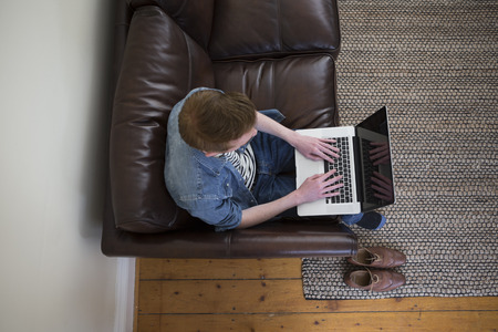 directly above: Overhead view of man using laptop on couch in living room