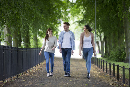 Portait of a group of students walking together outside in urban area. Three caucasian men and women walking at a university campus. photo