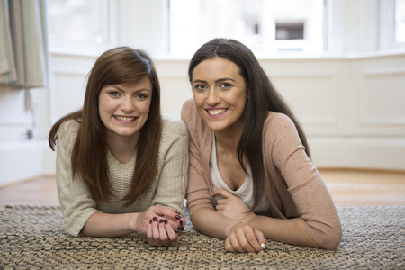 Portrait of two attractive, caucasian student girl friends at home together. photo