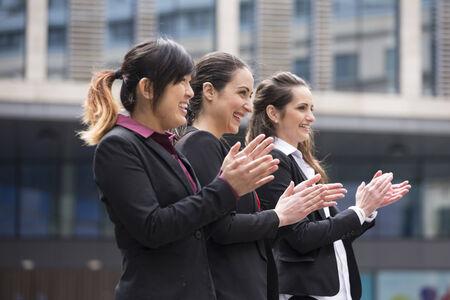 manos aplaudiendo: Retrato del grupo de tres ejecutivos de las mujeres aplaudiendo durante una reunión de negocios