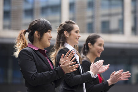 Group portrait of three female executives clapping hands during a business meeting photo