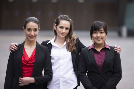 three people only: Portrait of three business women standing in a row. Interracial group of business women.