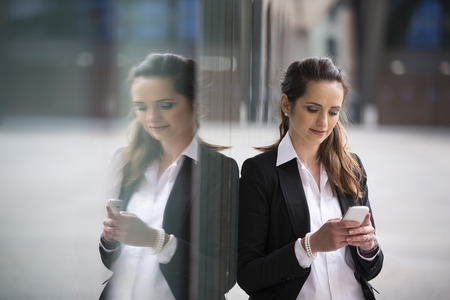 Portrait of a Caucasian businesswoman standing outside using mobile phone to send a message. photo
