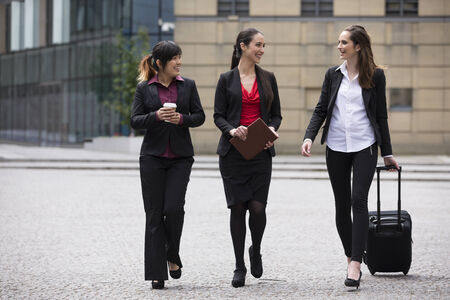 Three Happy Business women walking outside and talking to each other. photo