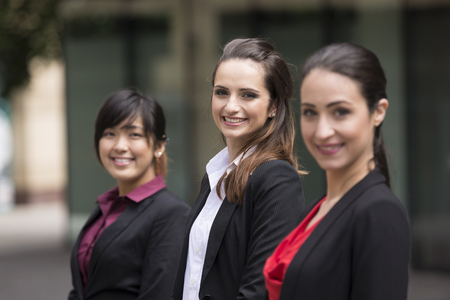three people only: Portrait of three business women. Shallow depth-of-field, focus used to highlight the woman in the middle. Interracial group of business women.