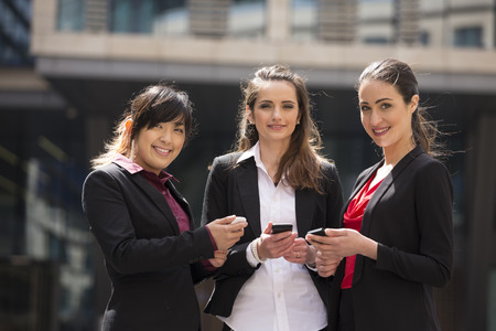 3 persons only: Three happy Business women looking at there mobile phones.
