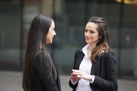 two people talking: Two business women standing outside talking to each other.