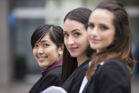 three people only: Portrait of three business women. Shallow depth-of-fieldfocus used to highlight the asian woman at the end of row.
