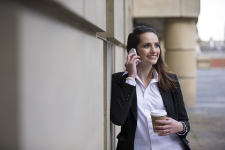 Portrait of a Caucasian businesswoman standing outside using mobile phone photo