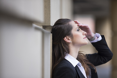 Angry business woman banging her head against a wall outside office building.