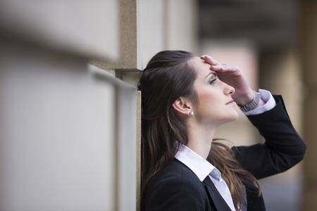 mujeres trabajando: Mujer de negocios enojada golpeando su cabeza contra una pared exterior del edificio de oficinas.
