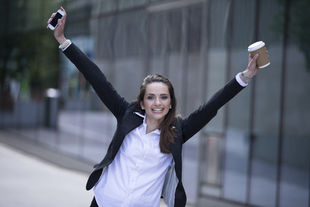 Portrait of a very happy caucasian businesswoman celebrating good news. Business woman with arms up in the air cheering. photo