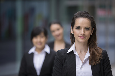 Portrait of three business women. Focus is on caucasian woman at the front. Interracial group of business women. photo