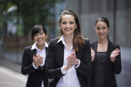Group portrait of three female executives clapping hands during a business meeting
