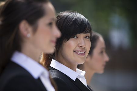 Portrait of three business women. Shallow depth-of-fieldfocus used to highlight the Asian woman in the middle. Interracial group of business women. photo