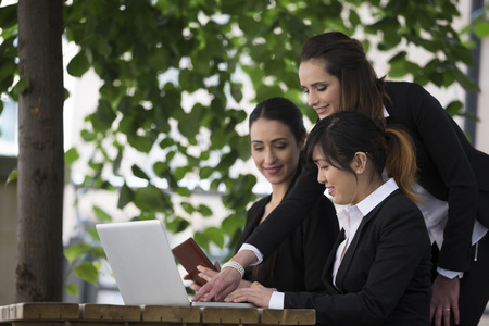 Three businesswoman working together on a laptop outdoors in modern city. photo