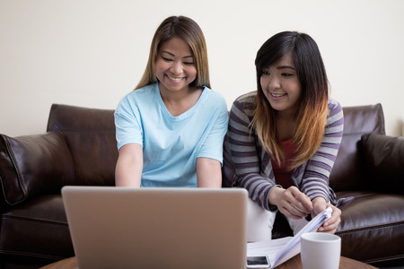 Two Asian female friends sitting at home, using a laptop pc. Lifestyle image of 2 asian girl firends relaxing. photo