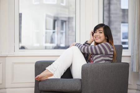 Portrait d'une jeune femme asiatique assis détente à la maison sur la chaise.