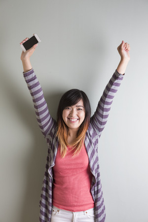 Portrait of happy Chinese woman celebrating good news with arms up in the air cheering. photo