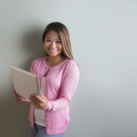 Happy Filipino woman in front of a green wall reading Tablet touch pad. photo