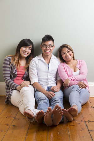 Group portrait of 3 happy Asian people. Looking at camera, in front of grey wall photo