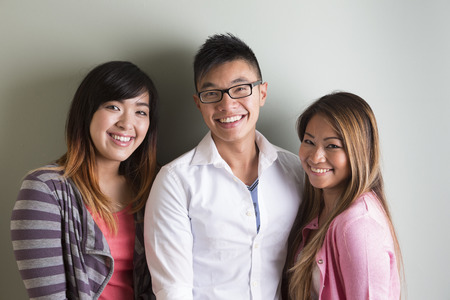 happy asian people: Group portrait of 3 happy Asian people. Looking at camera, in front of grey wall Stock Photo