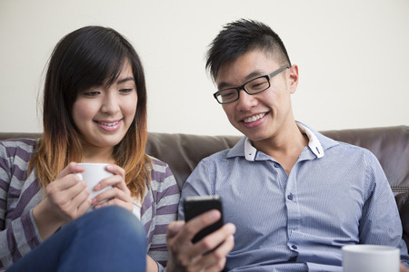 Chinese couple relaxing together and looking at a mobile phone. Happy young Asain couple sitting on a sofe together and looking at a smartphone. photo