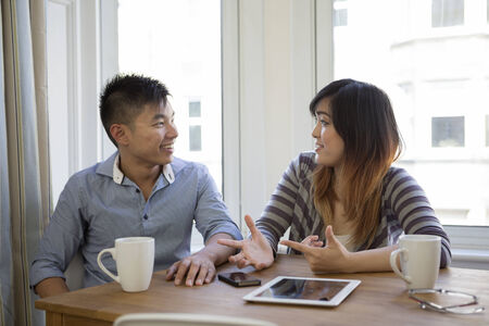 Chinese couple at home using a Tablet PC. Couple sitting at a table. photo