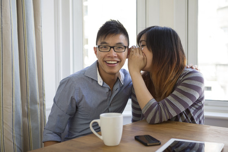 Asian woman whispering secrets in a friends ear. Her hand shielding her mouth. Happy Chinese couple at home together